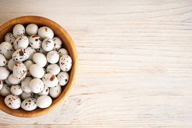 나무 배경에 나무 그릇에 부활절 달걀을 메 추 라 기