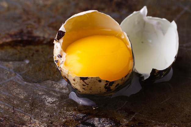 Quail egg broken on rustic table