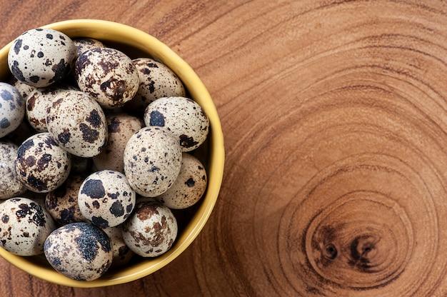 ボウルと木製のテーブルのウズラの卵