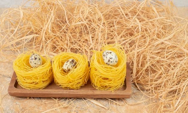 Uovo di quaglia su capellini di pasta su un tagliere accanto alla paglia, sul marmo.