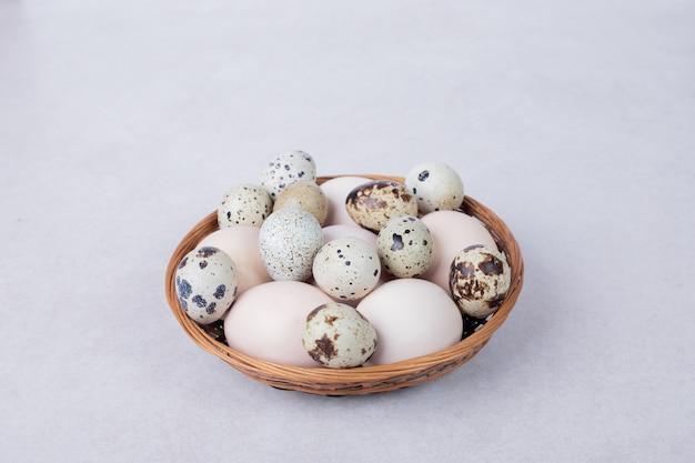 메 추 라 기 계란과 흰색 표면에 그릇에 닭고기 달걀.