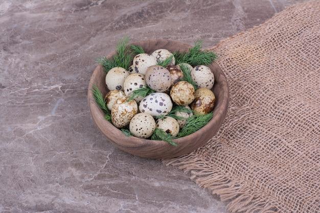 ウズラの卵とハーブを木製のカップに入れます。