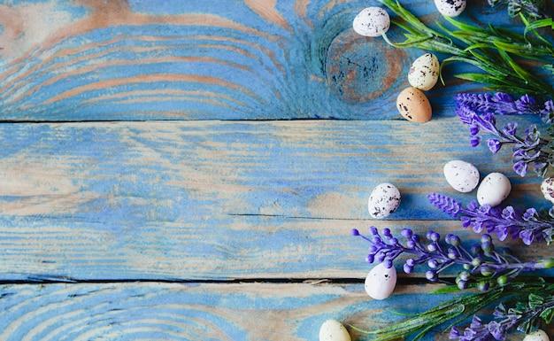낡은 푸른 나무 테이블에 메추라기 알과 샐비어 꽃.
