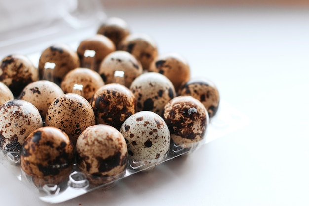 Quail eggs in a box on a white background copy space