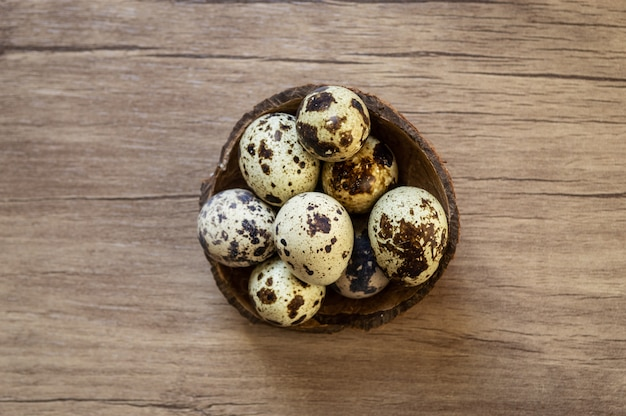 Quail eggs on brown wooden background. flat lay, top view. easter concept.