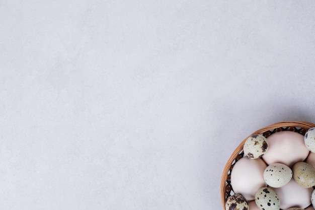 Uova di quaglia e uova di gallina in una ciotola sulla superficie bianca.