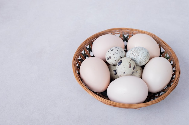 Quail eggs and chicken eggs in bowl on white surface.