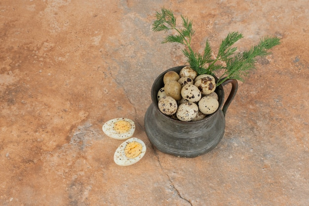 Uova di quaglia sulla tazza e uova sode sulla superficie del marmo