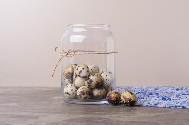 Uova di quaglia in un contenitore di vetro sul marmo.
