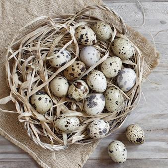 Перепелиные яйца в корзине на деревянном столе
