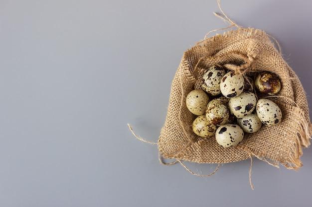 黄麻布の巣のウズラの卵、エレガントなイースターの背景、上面図、コピースペース、クローズアップ。