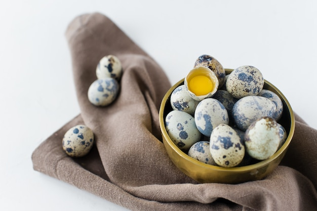 황금 그릇에 메추라기 계란, 깨진 계란 하나.