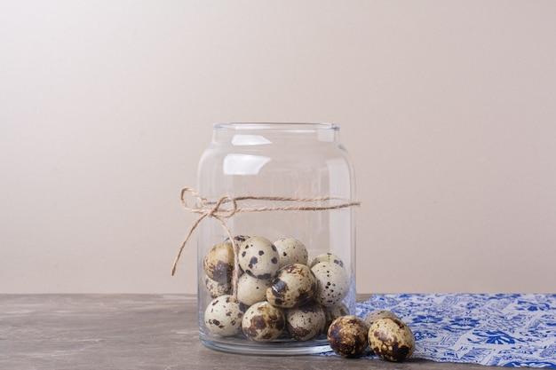 青いタオルの上の瓶の容器にウズラの卵