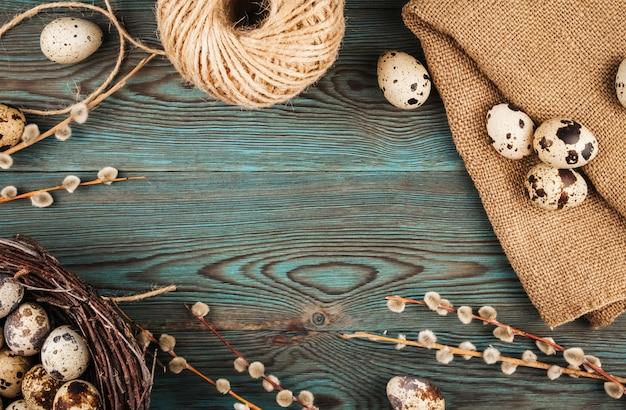 青い木製の背景コピースペースに巣、黄麻布、柳の小枝にウズラの卵。自然なイースター装飾フラットレイアウト