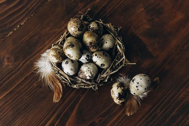 木製の背景に巣のウズラの卵