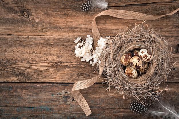 Перепелиные яйца в гнезде с цветами и лентой на деревянном фоне.