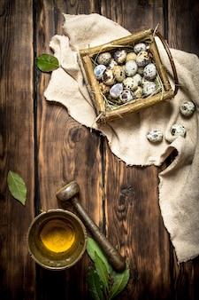 バスケットのウズラの卵と木製のテーブルの乳鉢で挽いたスパイス