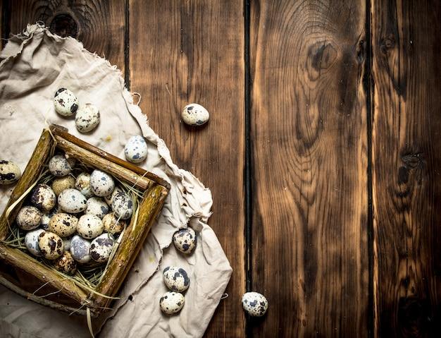 木製のテーブルの上のバスケットのウズラの卵。
