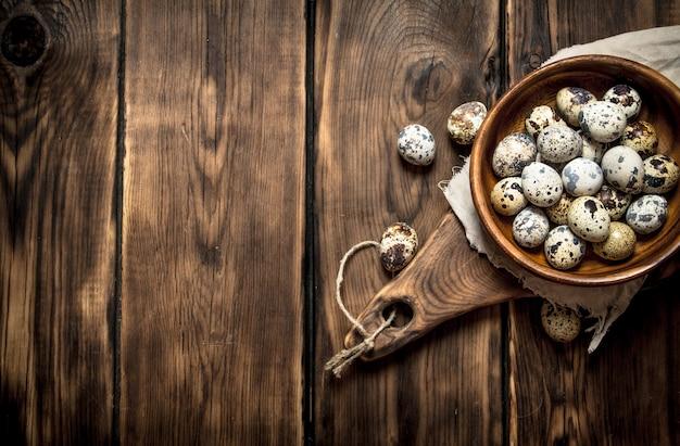 木製のテーブルのボウルにウズラの卵