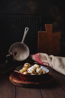 어두운 오래 된 표면에 금속 접시에 메 추 라 기 계란. 소박한 스타일. 톤 이미지.