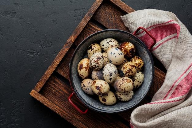 어두운 오래 된 표면에 금속 접시에 메 추 라 기 계란. 소박한 스타일