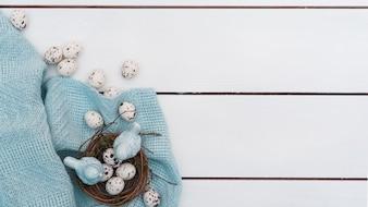木製のテーブルの上の巣でウズラの卵