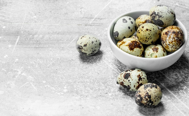Перепелиные яйца в миске. на деревенском столе.