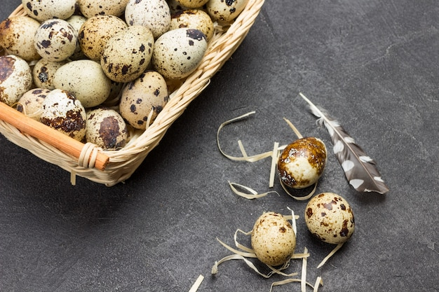 고리 버들 바구니에 메추라기 알. 계란과 테이블에 깃털. 평평하다. 공간 복사