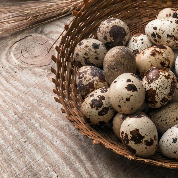 木製の背景に籐のバスケットのウズラの卵