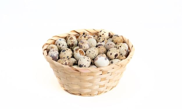 白い背景の上のバスケットの中のウズラの卵