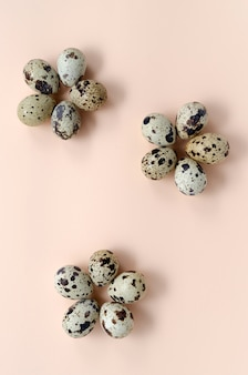 Quail eggs laid out in the form of flowers on a pink peach