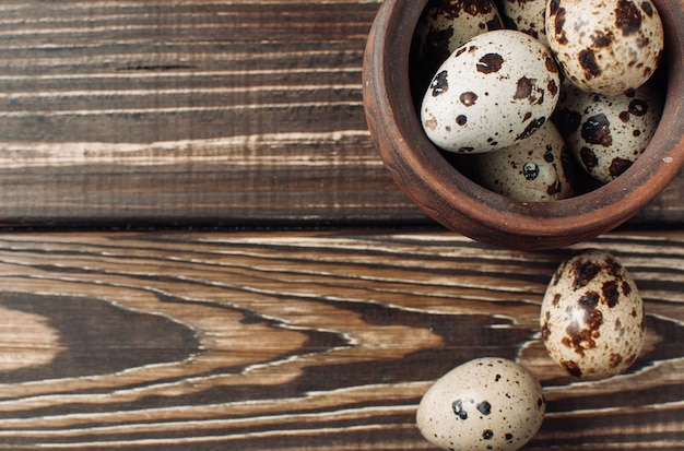 Quail eggs lie in a clay bowl and a couple of pieces fell out of the plate