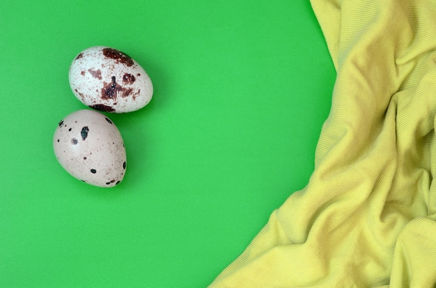 Quail eggs on a light green surface, top view
