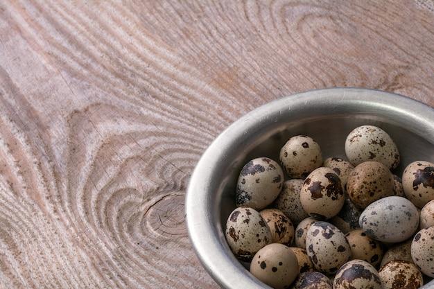 ウズラの卵の木製の背景に金属製のボウル