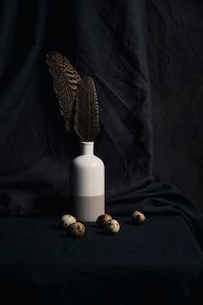 Uova di quaglia vicino a piume in vaso