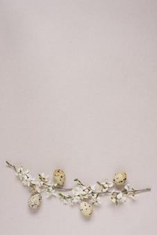 花と春の枝、ハッピーイースターグリーティングカードとベージュの背景にウズラの卵。