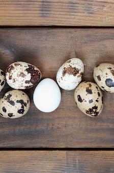 Перепелиные яйца на темно-коричневой деревянной поверхности, вид сверху, пустое место для текста, рецепт