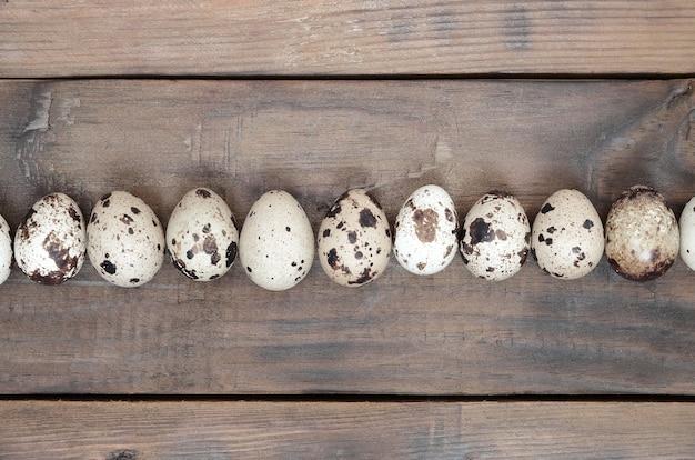 Перепелиные яйца на темно-коричневой деревянной поверхности