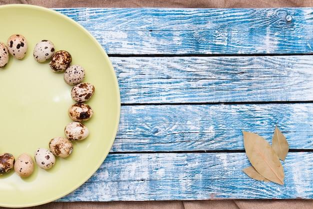 Перепелиные яйца на тарелке деревянный фон копией пространства