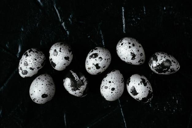 Перепелиные яйца на темном фоне. сырые перепелиные яйца. вид сверху