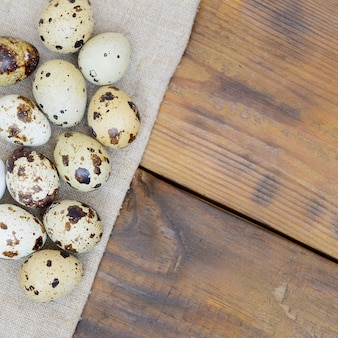 Перепелиные яйца на мешковине на темно-коричневой деревянной поверхности, вид сверху, пустое место для текста, рецепт