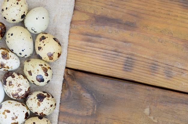 Перепелиные яйца на мешковине на темно-коричневой деревянной поверхности