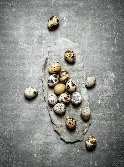 Перепелиные яйца на каменном столе.