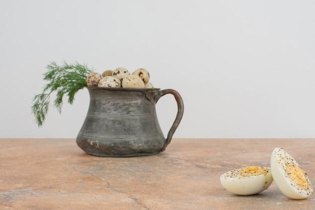 Перепелиные яйца на чашке и вареные яйца на мраморной поверхности