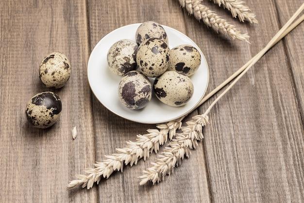 하얀 접시에 메추라기 알. 밀 이삭과 테이블에 두 개의 계란. 나무 테이블. 평면도.