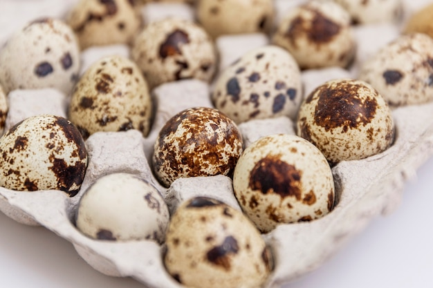 Quail eggs in a paper eco-friendly container. healthy diet food. close-up. white background.