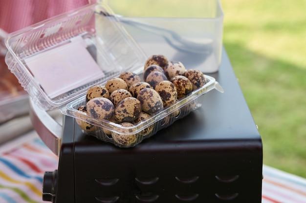 Quail eggs in plastic box on owen top
