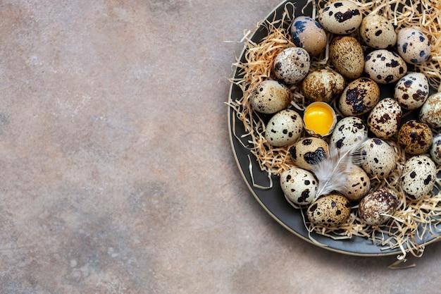 Quail eggs on a plate on a light sand surface