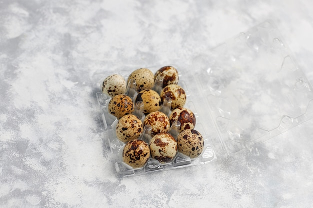 Quail eggs on a white-grey concrete