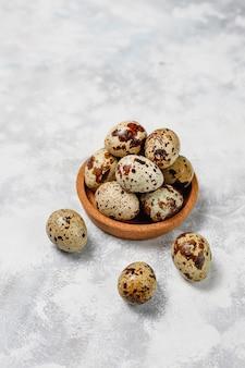 Quail eggs on a white-grey concrete